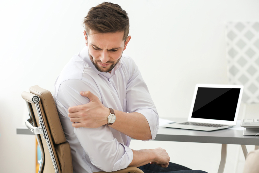Man with shoulder pain while at work.